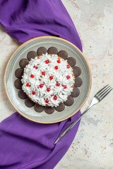 Torta vista dall'alto con crema pasticcera su piatto ovale scialle viola