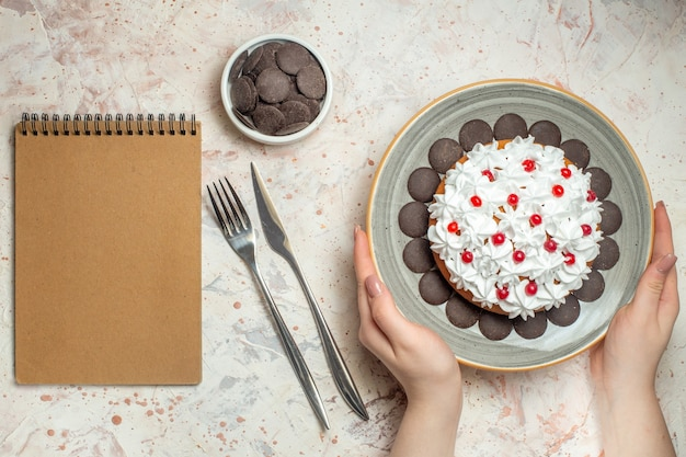 Top view cake with pastry cream on plate in female hand chocolate in bowl fork and dinner knife notebook