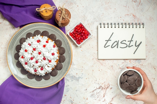 Top view cake with pastry cream on plate purple shawl cookies tied with rope berries in bowl chocolate bowl in female hand tasty written on notepad on white table