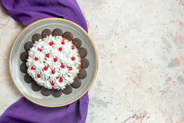 Top view cake with pastry cream on plate purple shawl
