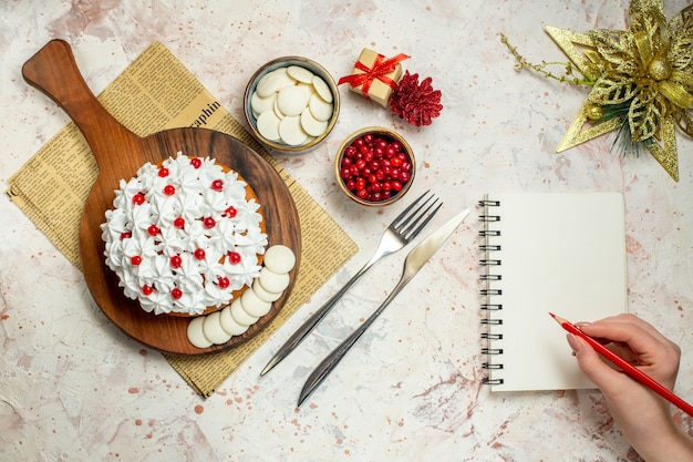 Top view cake with pastry cream on wood board on newspaper. xmas ornament, notebook and red pencil in woman hand
