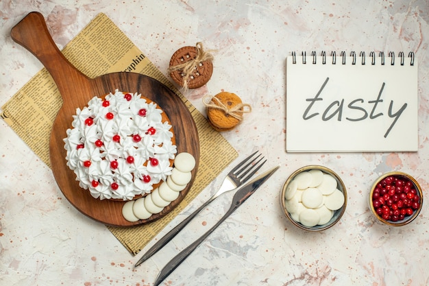 Top view cake with pastry cream on wood board. tasty written on notebook