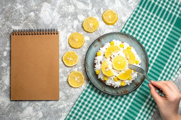 여성 손에 흰 생 과자 크림과 레몬 포크와 상위 뷰 케이크