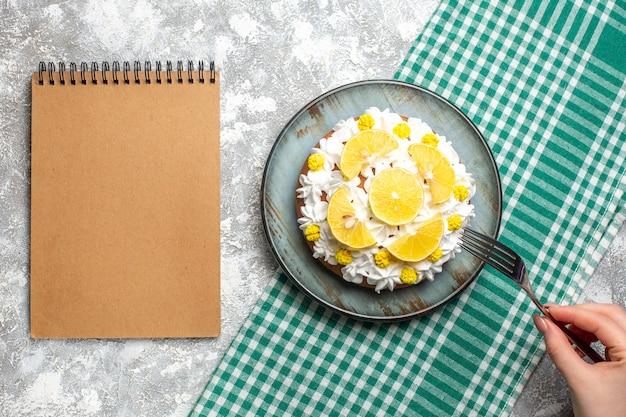 둥근 접시에 흰 생 과자 크림과 레몬 조각이있는 상위 뷰 케이크