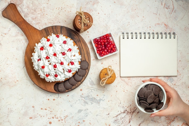 Top view cake with white pastry cream on chopping board bowl with berries chocolate bowl in woman hand cookies tied with rope on light grey table