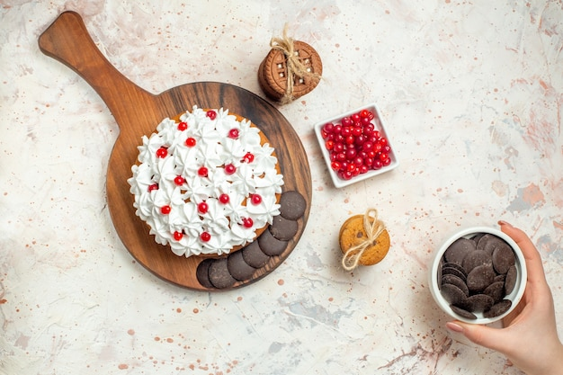 Top view cake with white pastry cream on cutting board bowl with berries chocolate bowl in female hand cookies tied with rope on light grey table