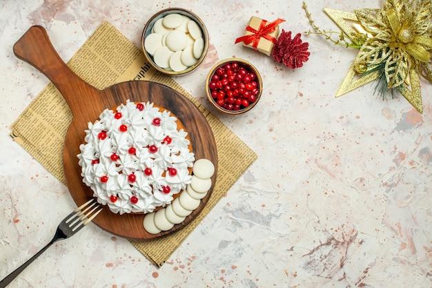 ホワイトチョコレートとベリーと新聞クリスマスオーナメントボウルの木製ボードに白いペストリークリームフォークとトップビューケーキ