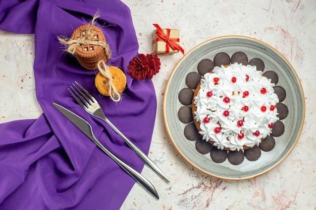 Вид сверху торт с белым кондитерским кремом на тарелке, печенье, перевязанное веревочной вилкой и обеденным ножом на фиолетовой шали