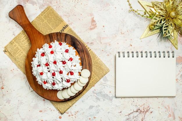 신문 및 크리스마스 장식에 나무 보드에 흰색 과자 크림과 함께 상위 뷰 케이크