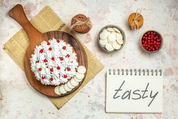 신문에 나무 보드에 흰색 과자 크림과 함께 상위 뷰 케이크. 노트북에 맛있는