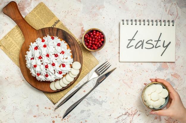 신문에 나무 보드에 흰색 과자 크림과 함께 상위 뷰 케이크. 여성의 손에 그릇에 화이트 초콜릿입니다. 노트북에 맛있는
