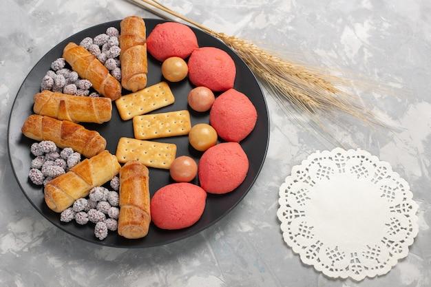 白い背景の上のプレートの内側にキャンディーとクラッカーが付いた上面図のケーキとベーグルケーキビスケットクッキーシュガースイートパイ