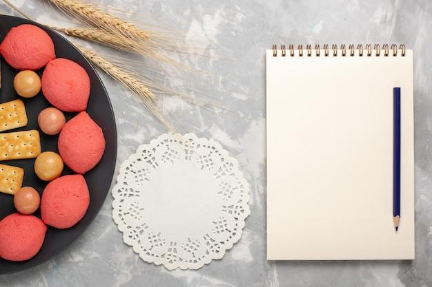 白い机の上のプレートの内側にキャンディーとクラッカーが付いた上面図のケーキとベーグルケーキビスケットクッキーシュガースイートパイ