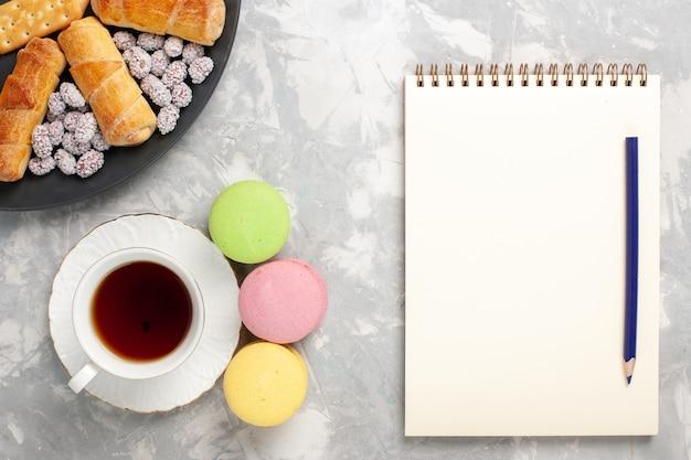ライトホワイトの背景にキャンディクラッカーとお茶のトップビューケーキとベーグルケーキビスケットクッキーシュガースイートパイ