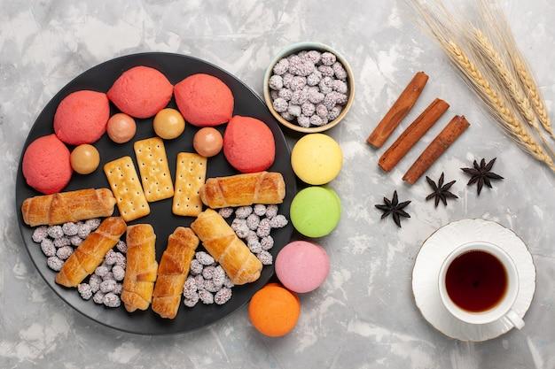 上面図のケーキとベーグル、白い表面にキャンディークラッカーとお茶のカップケーキビスケットクッキーシュガースイートパイ
