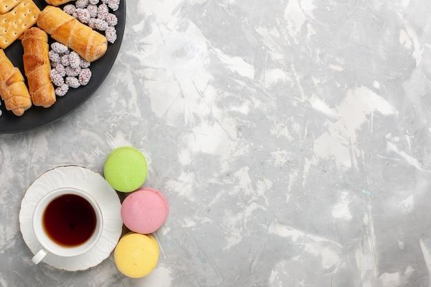 사탕 크래커와 흰색 책상 케이크 비스킷 쿠키 설탕 달콤한 파이에 차 한잔 상위 뷰 케이크와 베이글