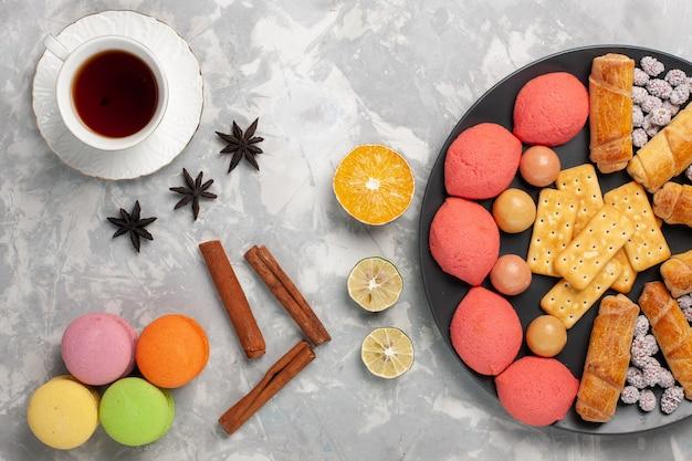 トップビューケーキとベーグルとキャンディークラッカーと白い表面のお茶のカップケーキビスケットクッキーシュガースイートパイ