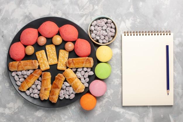 白い背景の上のキャンディークラッカーとフレンチマカロンとトップビューのケーキとベーグルケーキビスケットクッキーシュガースイートパイ