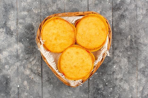 Вид сверху торты приготовленные вкуснятина внутри корзины на серой деревенской деревянной