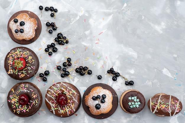 Una vista dall'alto torte e ciambelle a base di cioccolato con frutta e caramelle