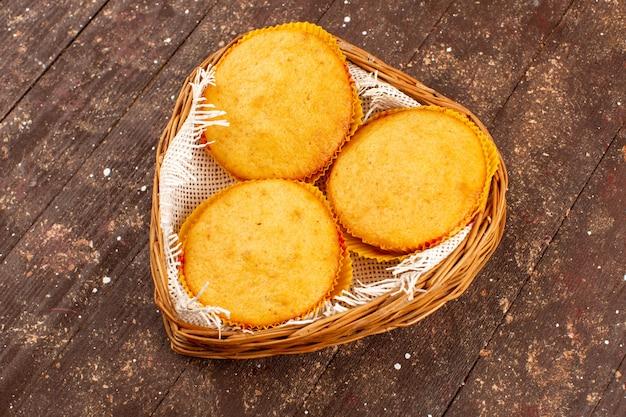 Вид сверху пирожные вкусные вкусные внутри корзины на коричневом полу