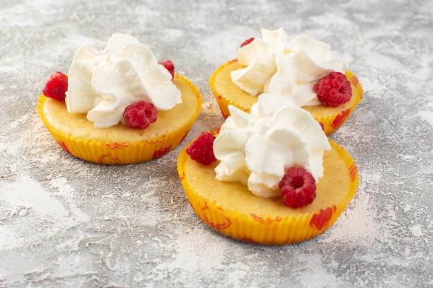 Вид сверху торты с кремом вкусная запеченная с малиной на сером фоне сахарная сладкая выпечка бисквитный крем