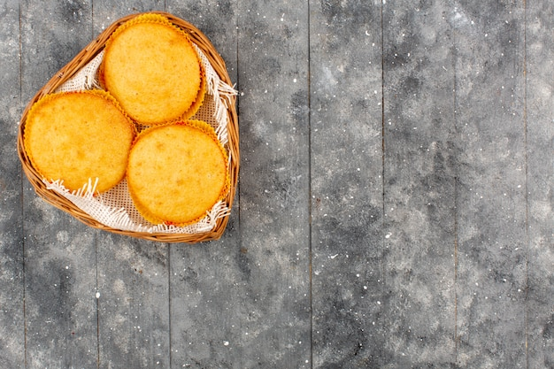 Вид сверху пирожные вкусные круглые внутри корзины на сером полу