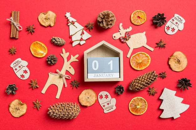 Top view of calendar decorated with festive toys and christmas symbols reindeers and new year trees. the first of january. holiday concept
