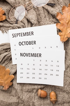 Top view of calendar with autumn leaves and glasses