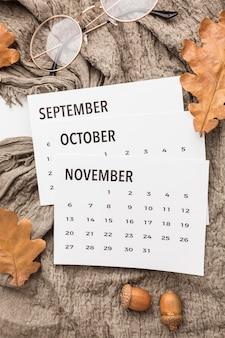 Vista dall'alto del calendario con foglie autunnali e bicchieri