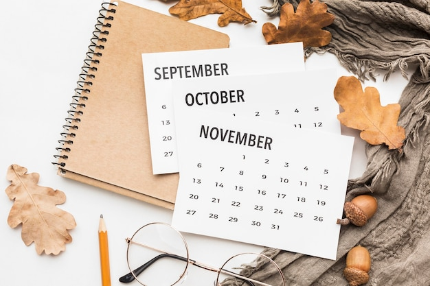 Top view of calendar with glasses and autumn leaves