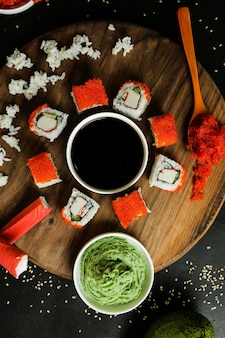 Top view california rolls on a stand with ginger soy sauce avacado boiled rice and wasabi