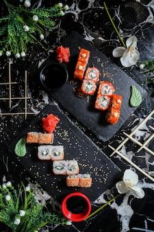 Вид сверху суши-роллы калифорния с роллами филадельфия на подставках с соевым соусом васаби и имбирем с цветами