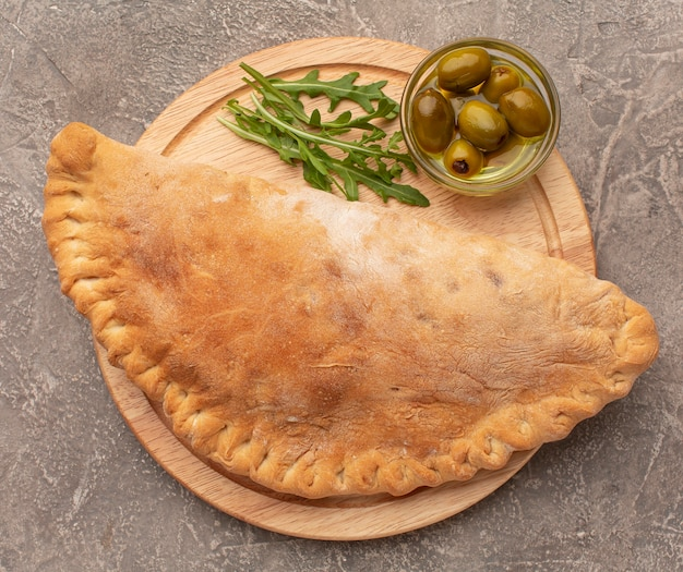 Top view calzone, herbs and olives