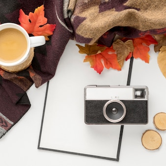 Top view of camera with autumn leaves and coffee