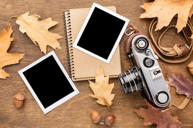 Top view of camera with photos and autumn leaves