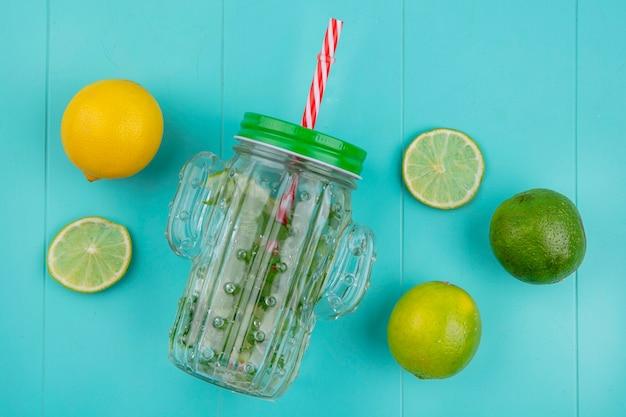 Vista dall'alto della lattina di acqua con verdure e lime con limone su una superficie blu