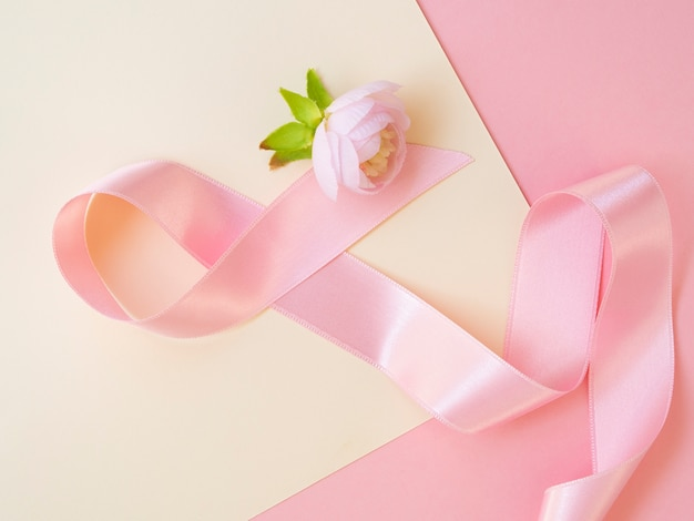 Top view cancer concept with pink ribbon and rose