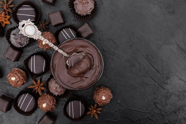 Вид сверху конфеты и растопленный шоколад с копией пространства
