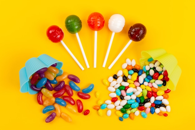 A top view candies and lollipops sweet tasty isolated on yellow