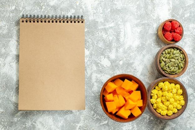 Vista dall'alto caramelle e zucca con semi e blocco note su sfondo bianco quaderno color caramella frutta