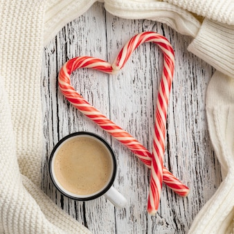 Top view of candy canes in heart shape with cup of hot cocoa