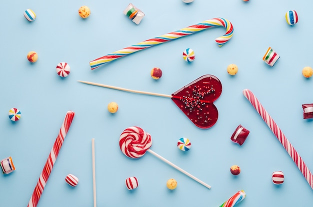 Top view of candy canes and lollipops on a light blue background