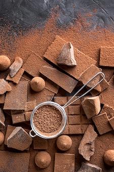 Vista dall'alto di caramelle e cioccolato con setaccio e cacao in polvere