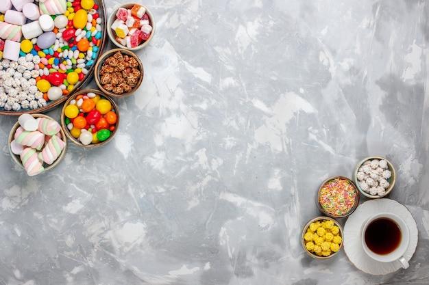 上面図キャンディー組成物異なる色のキャンディーとマシュマロと白い机の上のお茶砂糖キャンディーボンボン甘いコンフィチュール