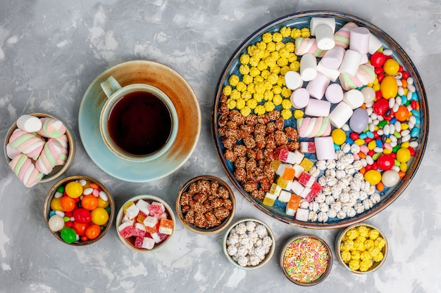 Top view candy composition different colored candies with marshmallow and cup of tea on white desk sugar candy bonbon sweet confiture