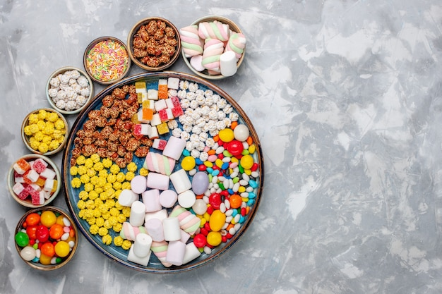 Top view candy composition different colored candies with marshmallow inside pots on light white desk sugar candy bonbon sweet confiture