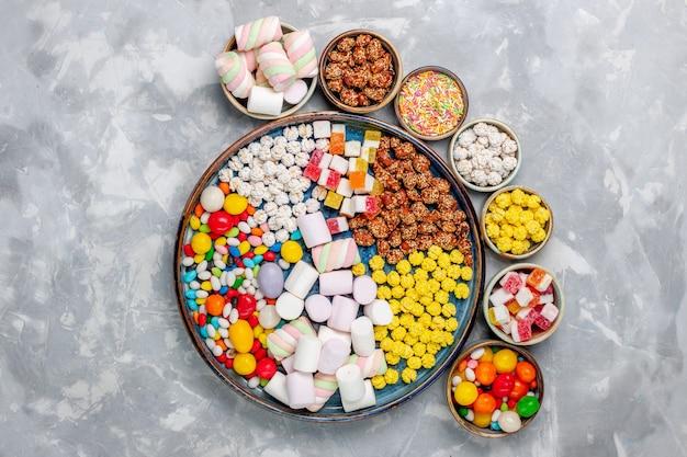 上面図キャンディー組成物白い机の上の鍋の中にマシュマロが入ったさまざまな色のキャンディーシュガーキャンディーボンボン甘いコンフィチュールティー