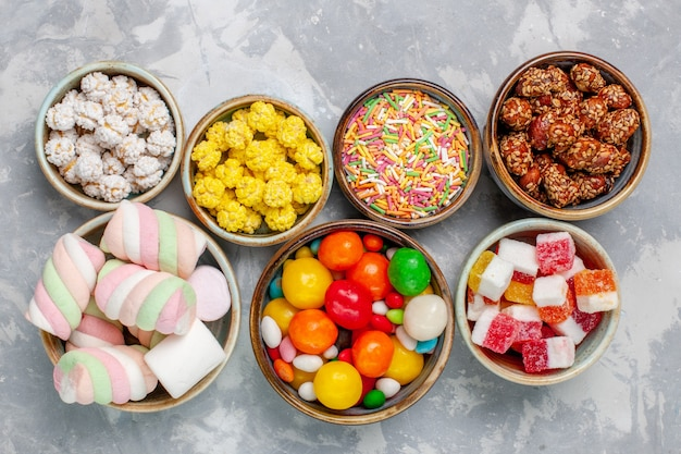 Top view candy composition different colored candies with marshmallow inside pots on the white desk sugar candy bonbon sweet confiture