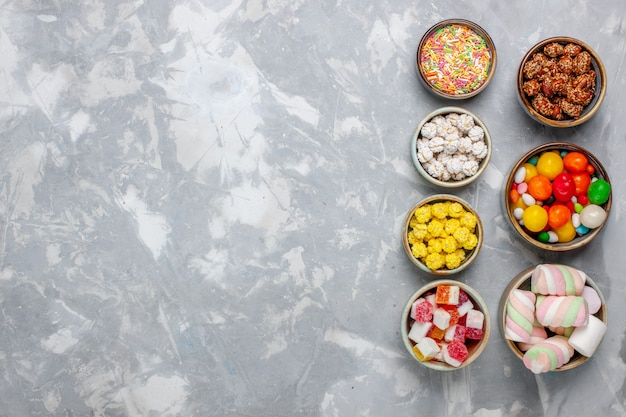 Top view candy composition different colored candies with marshmallow inside pots on white wall sugar candy bonbon sweet confiture